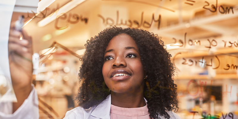 Mastercard Foundation Scholar Charity Bhebhe writes calculations on glass with whiteboard markers while wearing a lab coat. Her ASU research earned her the prestigious Gates Cambridge Scholarship for her doctorate.